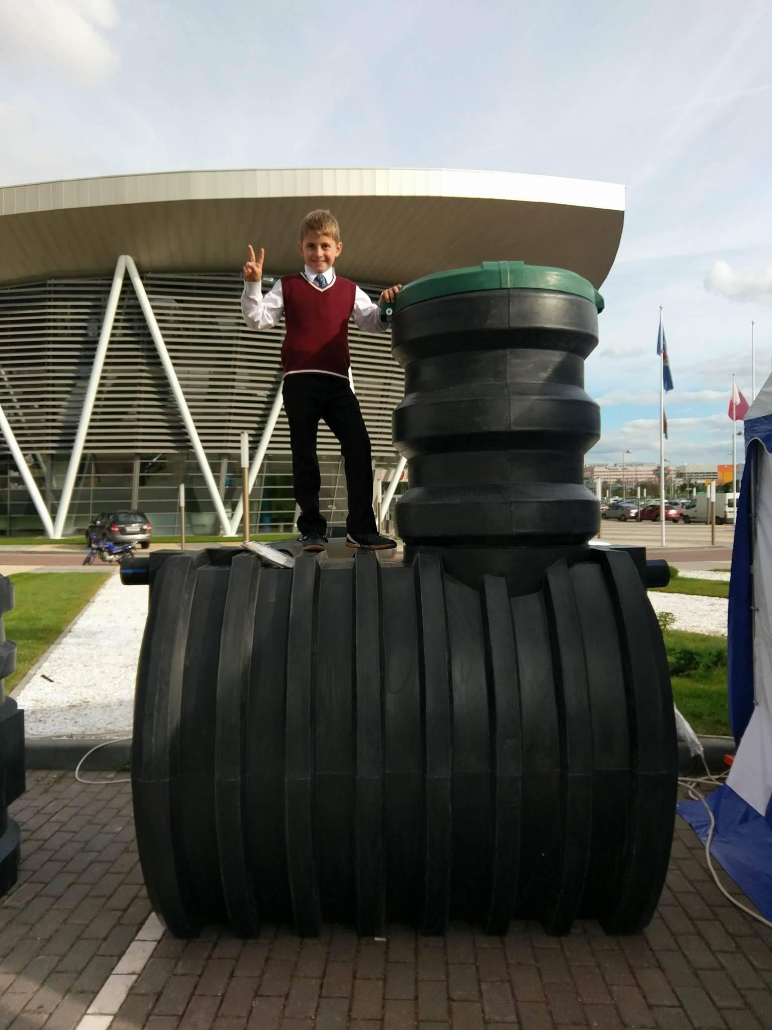 Септик для загородного дома автономной канализации на выставке в Минске - на септике стоит мальчик - сын директора завода. Септик под весом мальчика не прогнулся ни на миллиметр